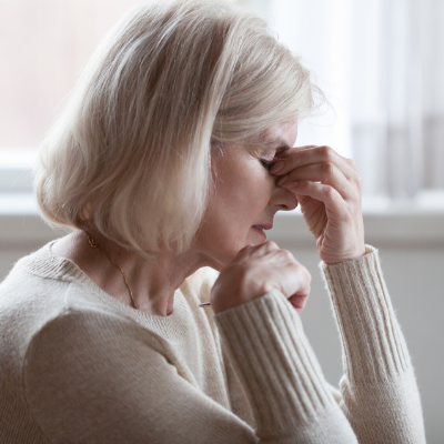 tired senior female caregiver with eyes closes