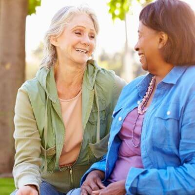 two senior women talking together outside