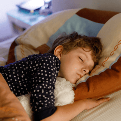 male child sleeping in bed with teddy bear