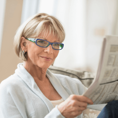 woman sitting at home reading the newspaper