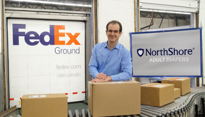 NorthShore Founder, Adam Greenberg with packages in Buffalo Grove, Illinois warehouse near Fedex truck