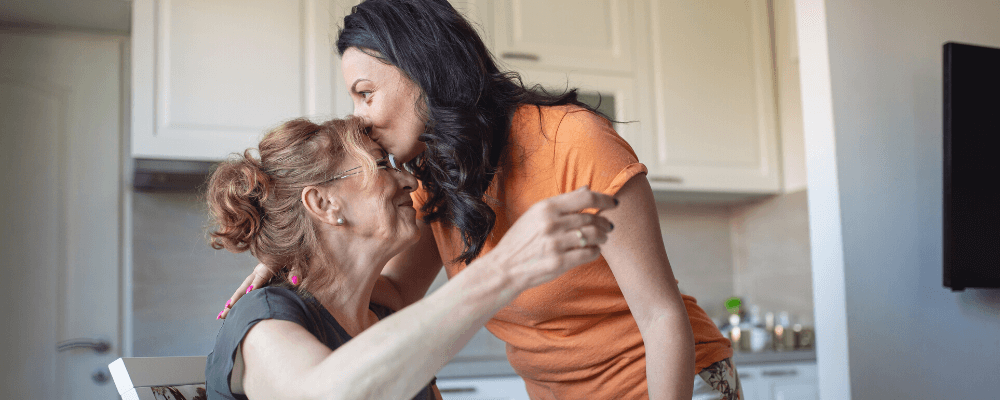 daughter kissing mother with Parkinson's on the forehead in kitchen
