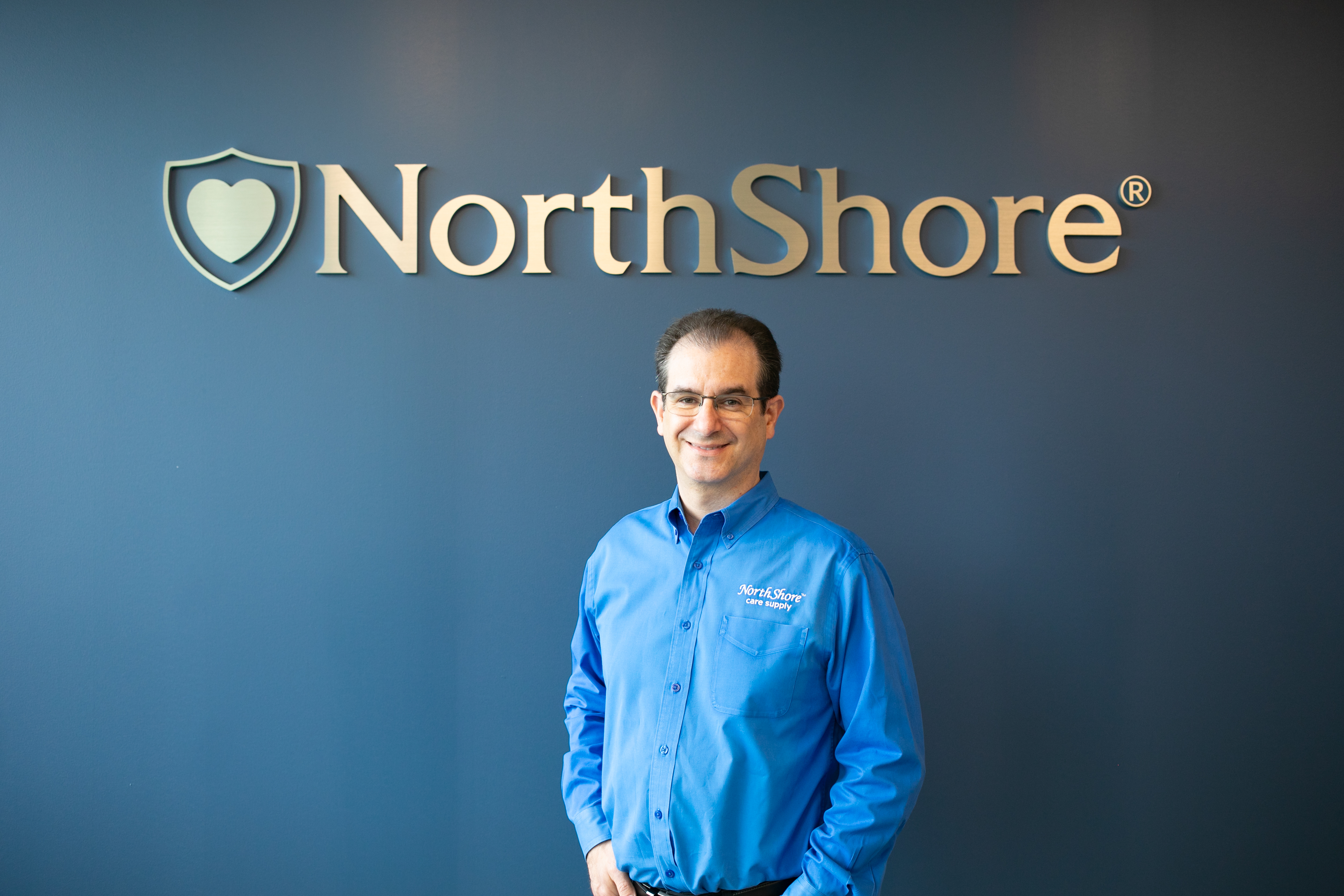 Founder, Adam Greenberg in front of NorthShore interior sign