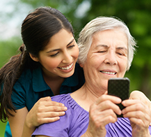 young woman and senior woman looking at a mobile device